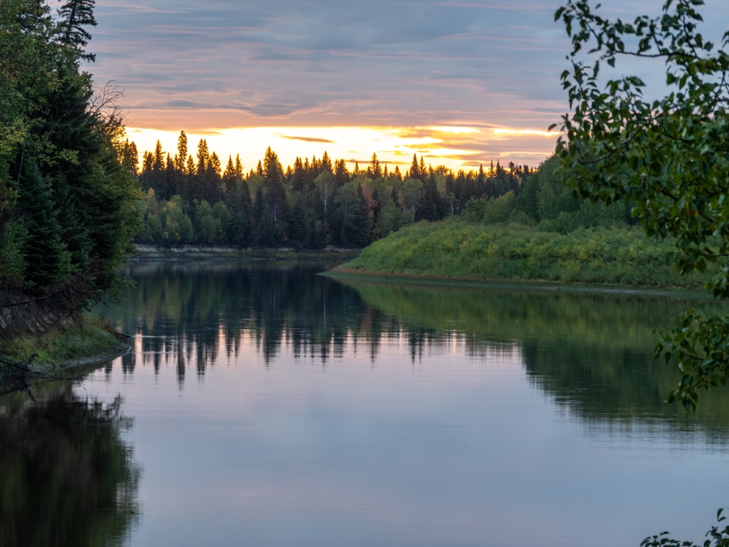 Sunrise illuminates the sky below a cloud layer. A wide, flat river winds among forested banks.