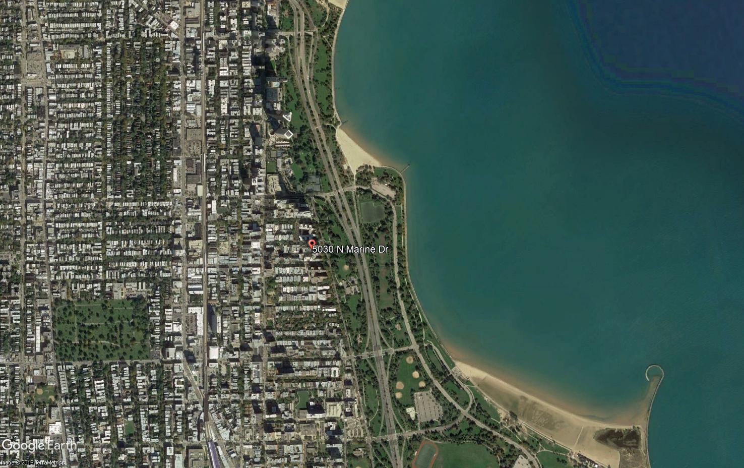 Aerial view of rows upon rows of buildings on the left, with a green buffer and the shores of Lake Michigan on the right.