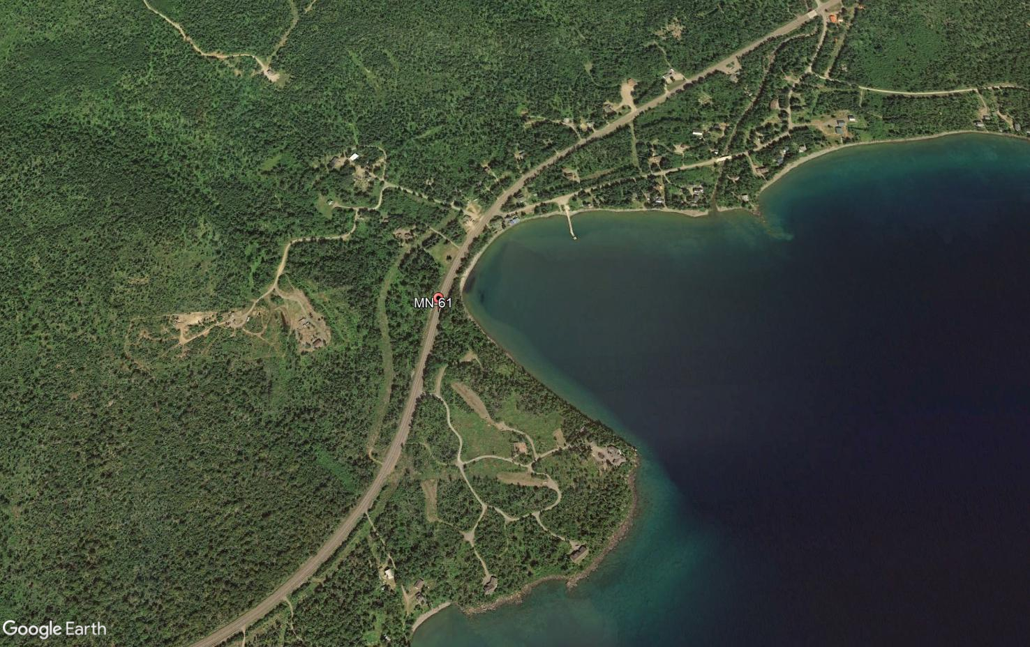 Aerial view of a forested area with some small roads and dispersed buildings, with Lake Superior in the right side of the photo.