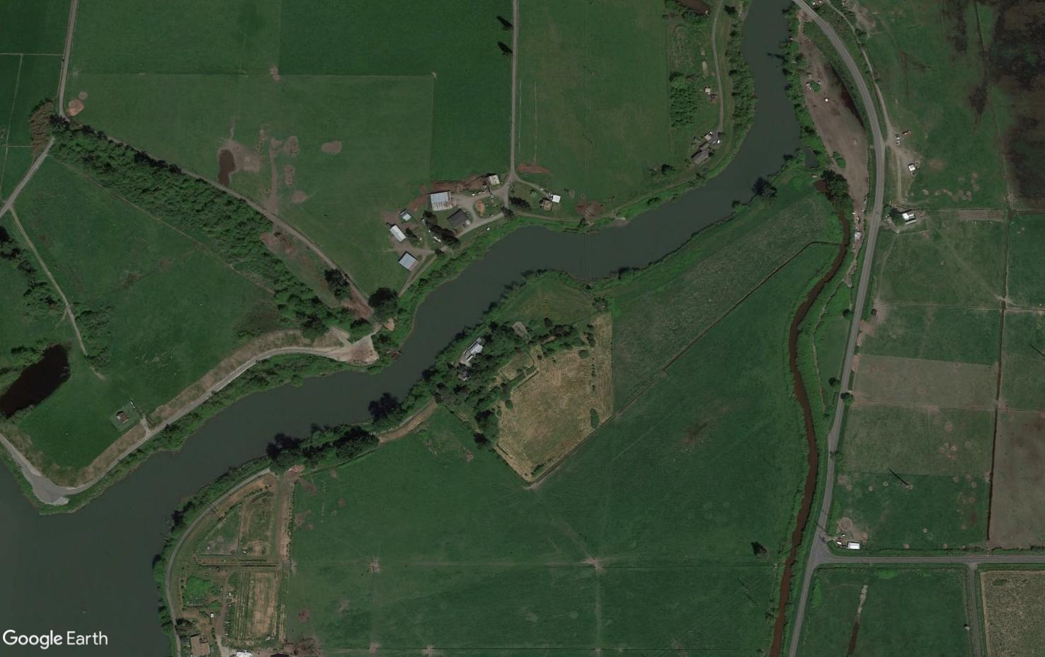 Aerial view of farm area along a river. My property has a growing green buffer around it.