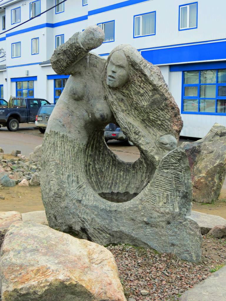 A large stone carving depicts a fingerless, angry mermaid rises up and whirls the water into waves.