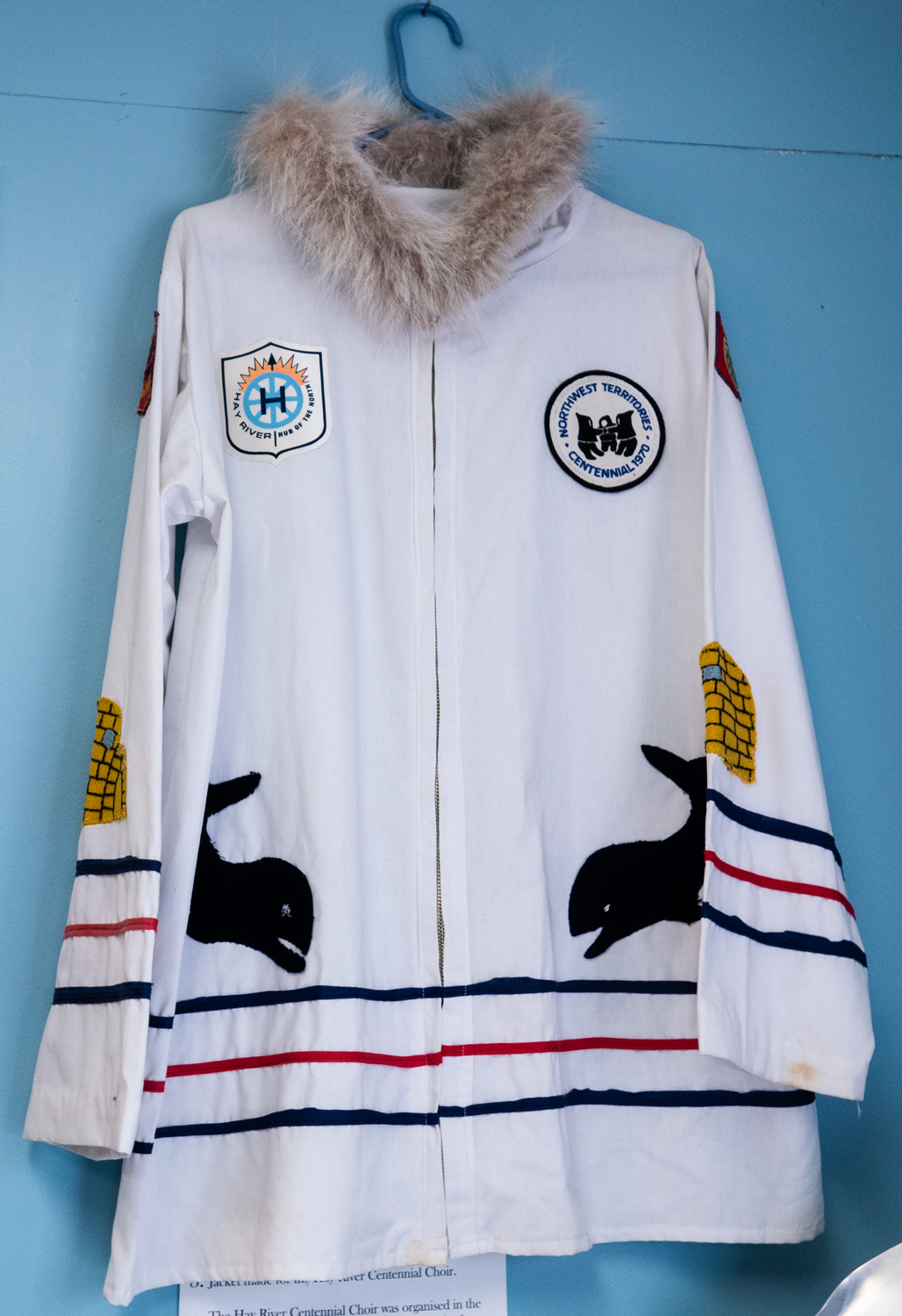 A white parka like jacket hangs on a wall. The jacket has a fur collar, three stripes across the bottom and lower sleeves, two whales swimming toward each other, and symbolic patches.