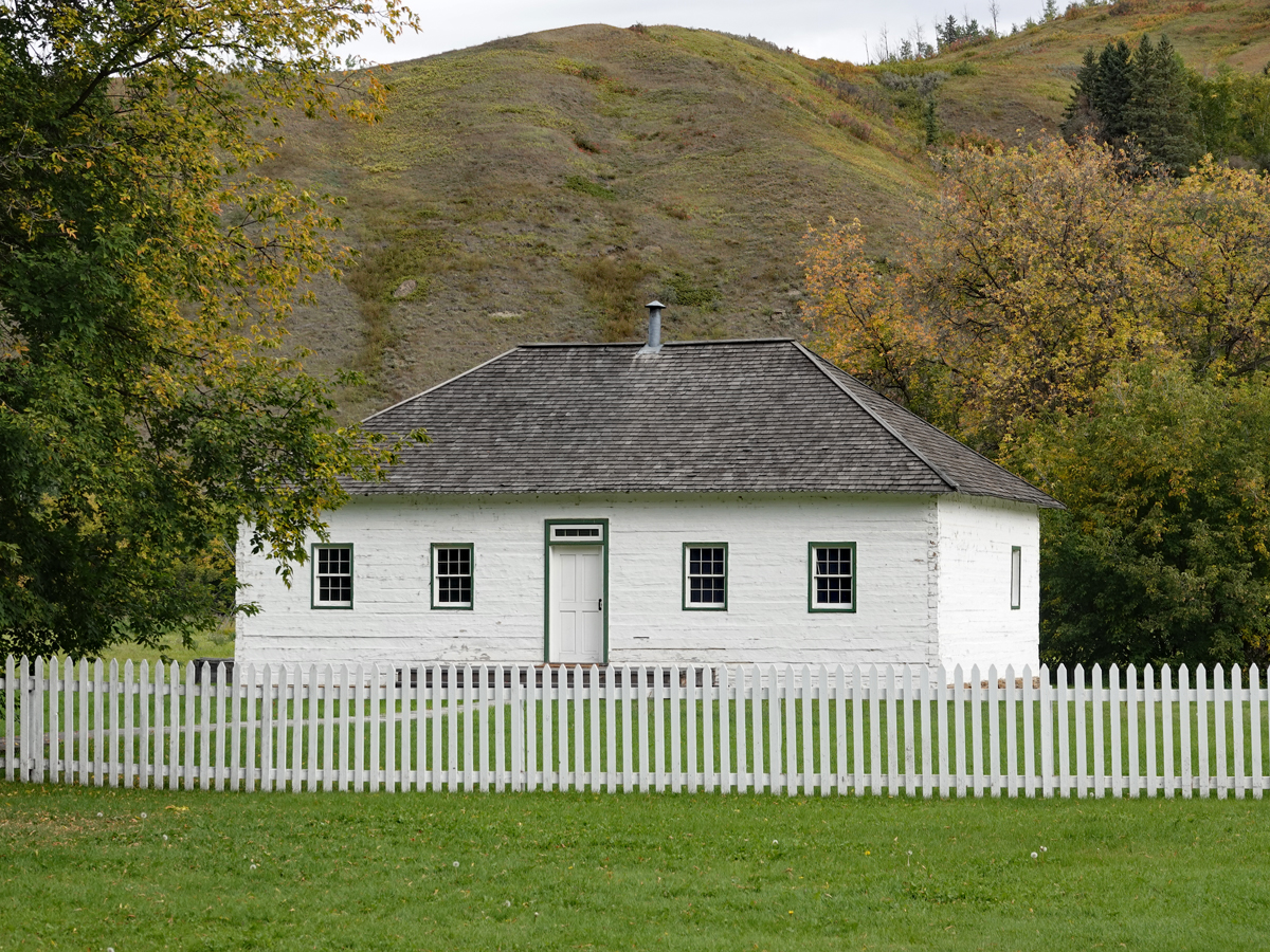 A small white building with tidy picket fence stands before a sandy hill.