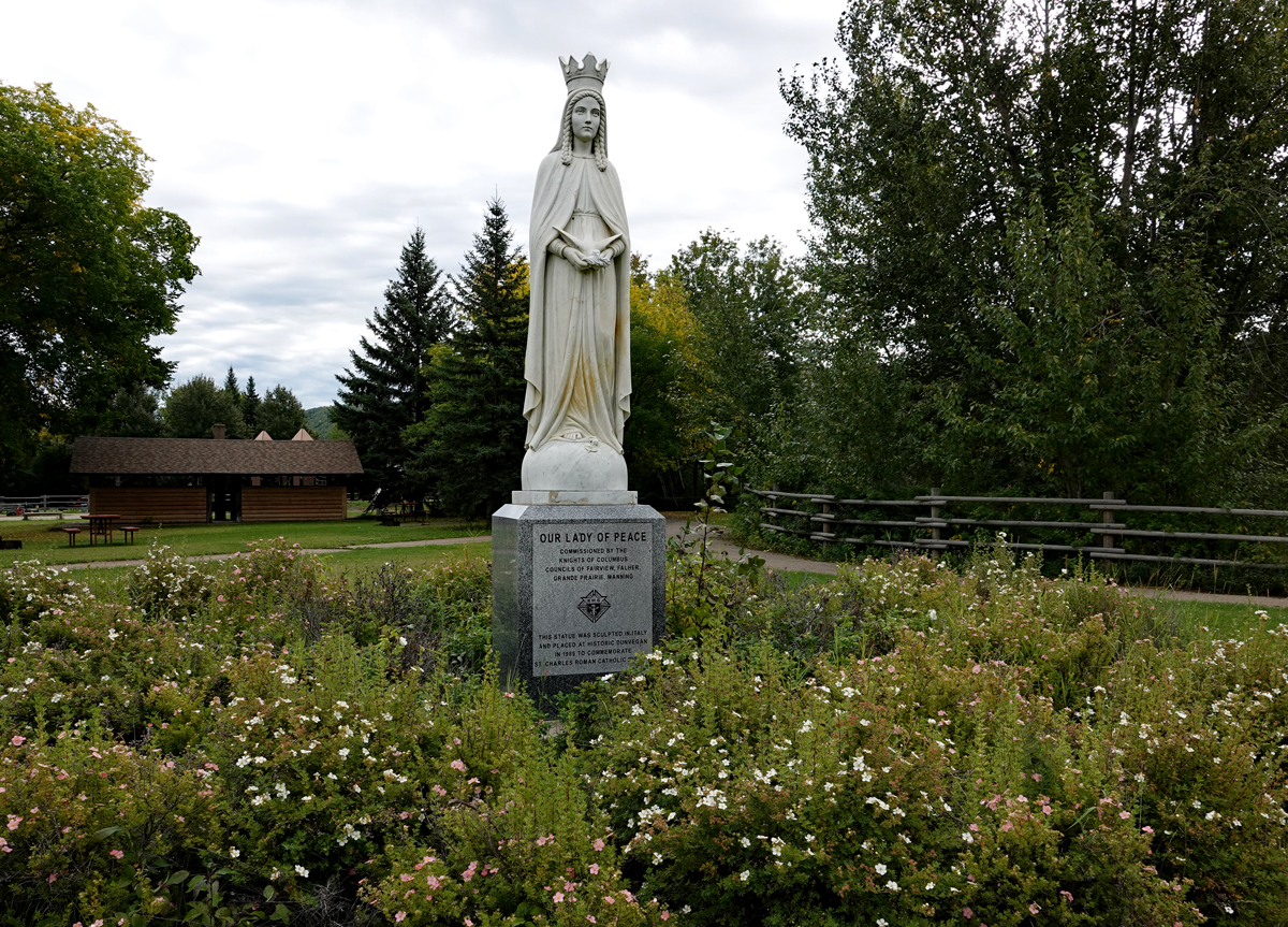 A white statue of the Virgin Mary wearing a crown rises above a pedestal with sign, surrounded by wild rose shrubs.