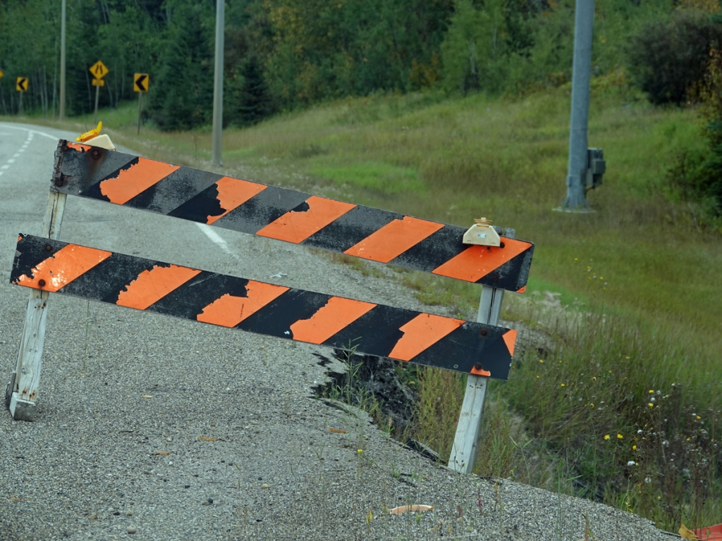 An orange and black striped barricade blocks people from a broken part of the road.