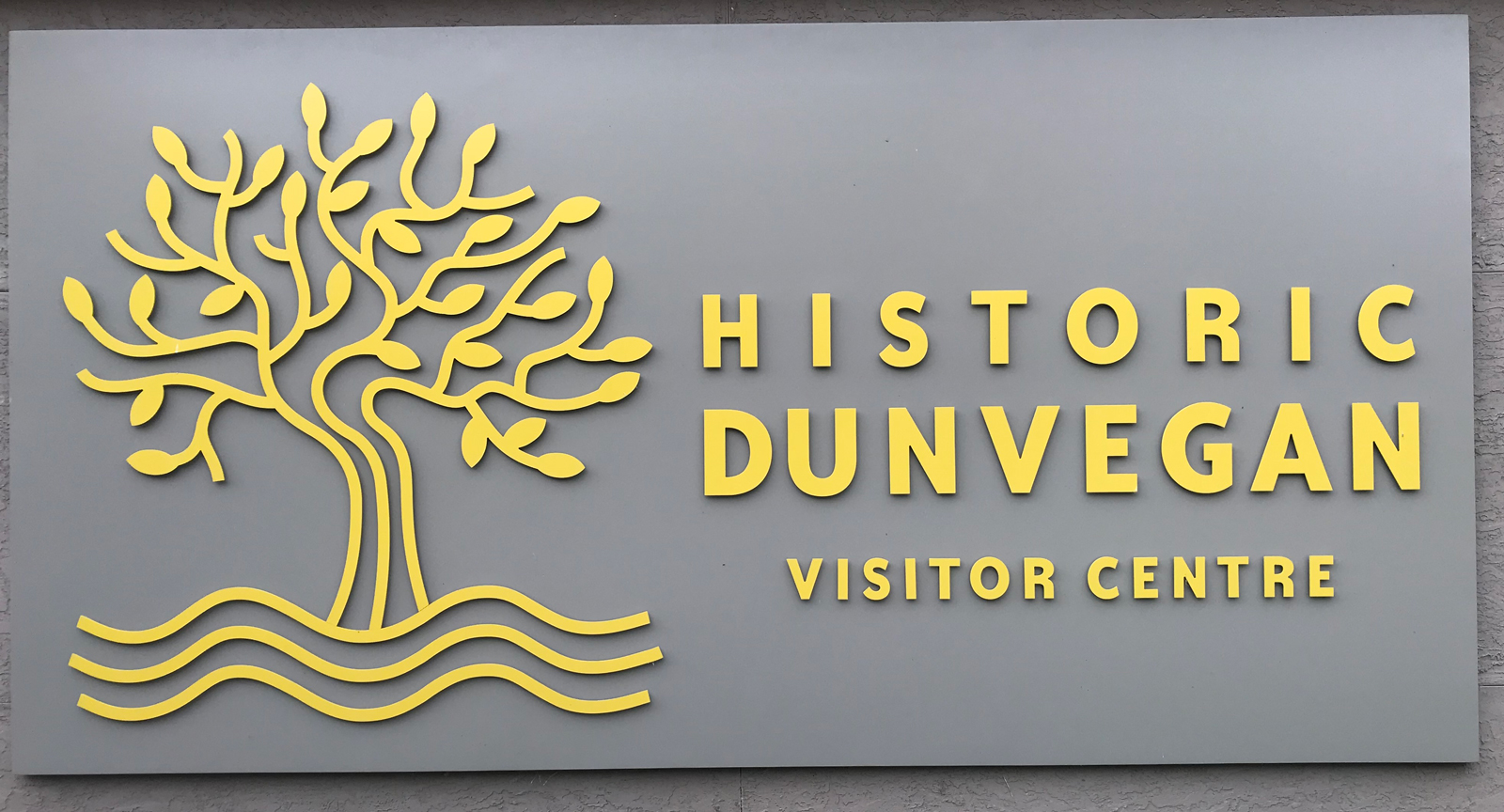 A grey sign with yellow text and graphic shows a Dunvegan Maple over three curving lines representing the Peace River.