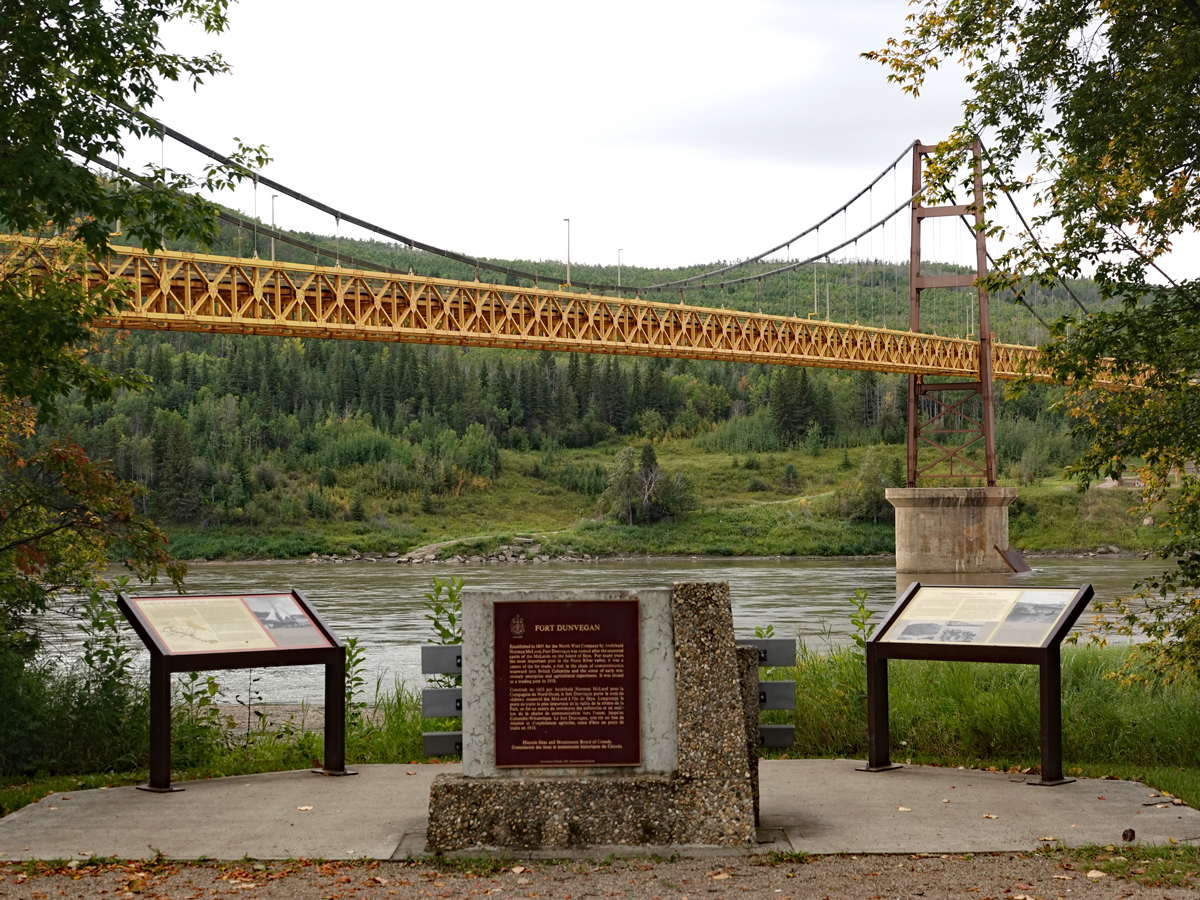 Interpretive signage and a plaque mark a view spot by the Peace River, with the yellow span of the Dunvegan suspension bridge overhead.