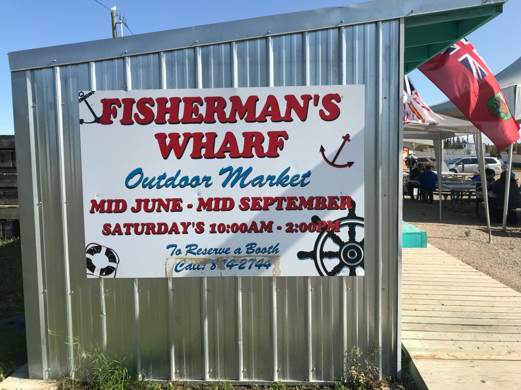 A sign on the side of a metal shed advertises the Saturday Market at Fisherman's Wharf.