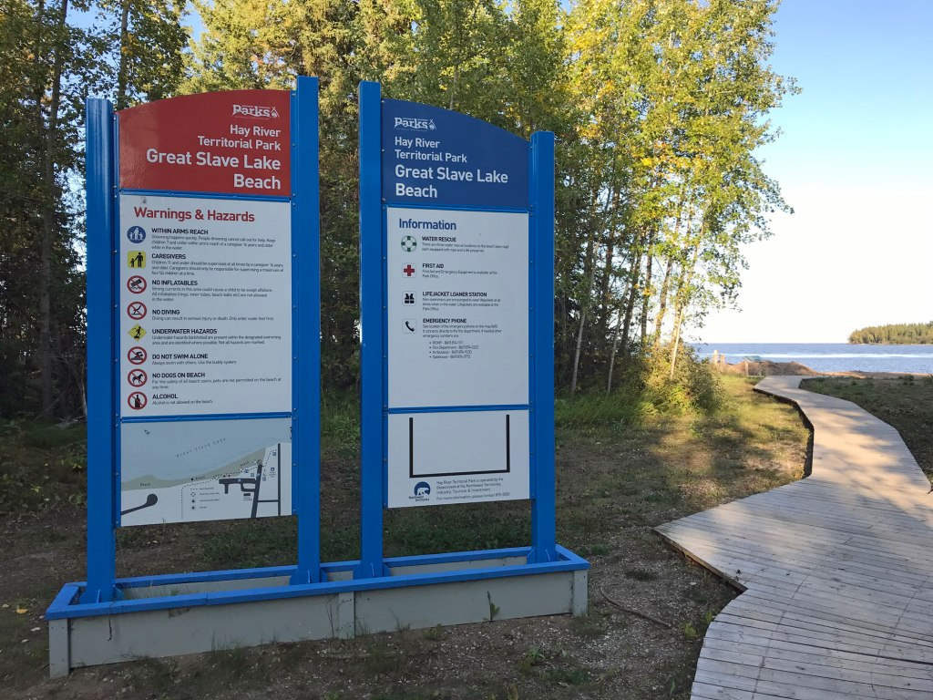 An elegant sign installation marks Great Slave Lake Beach at Hay River Territorial Park. A boardwalk runs past the blue sign mounts, leading to the water in the distance.