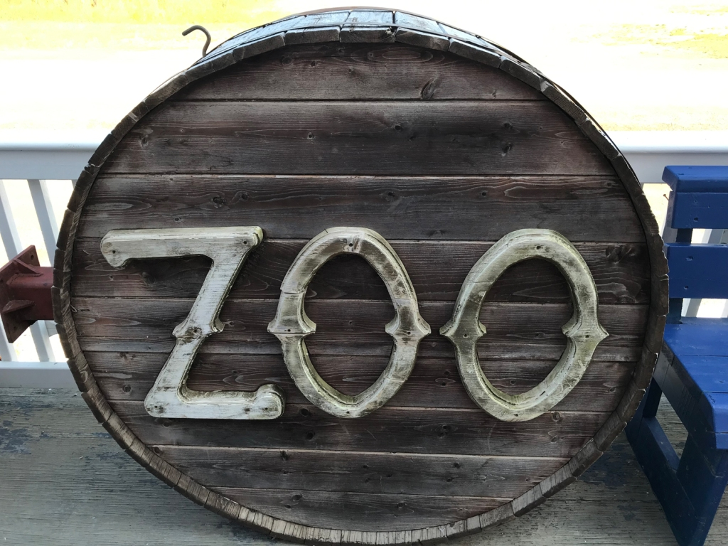 "A round barrel with carved wooden letters in light grey fixed to the bottom. The letters spell out ""zoo""."
