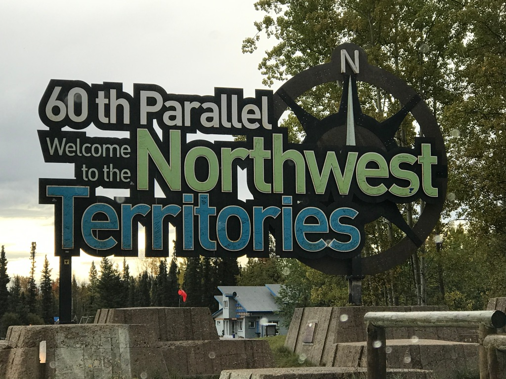 """A large, colorful sign reads """"60th Parallel- Welcome to the Northwest Territories"""". A compass pointing north is included at the right of the sign."""