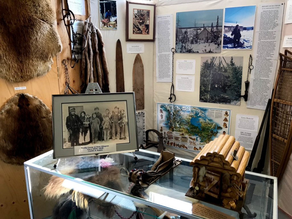 A booth wall and display case show gear and furs, along with photos, maps, and newspaper articles.