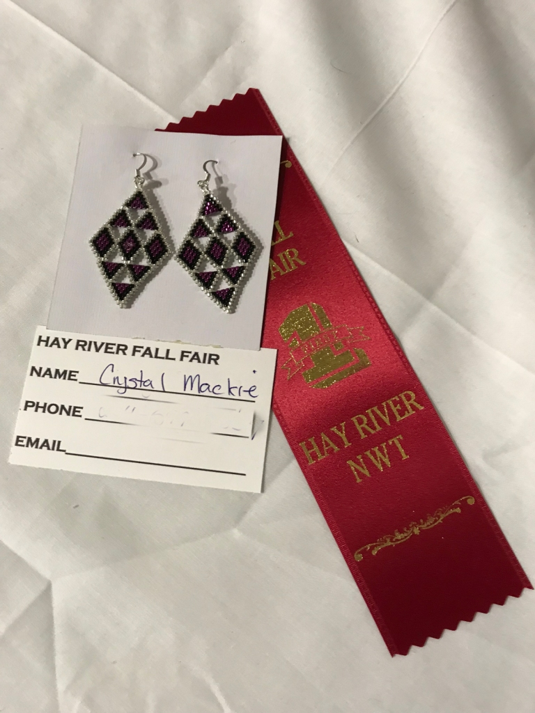 Two beaded earrings are pinned to a card with an award ribbon lying underneath.