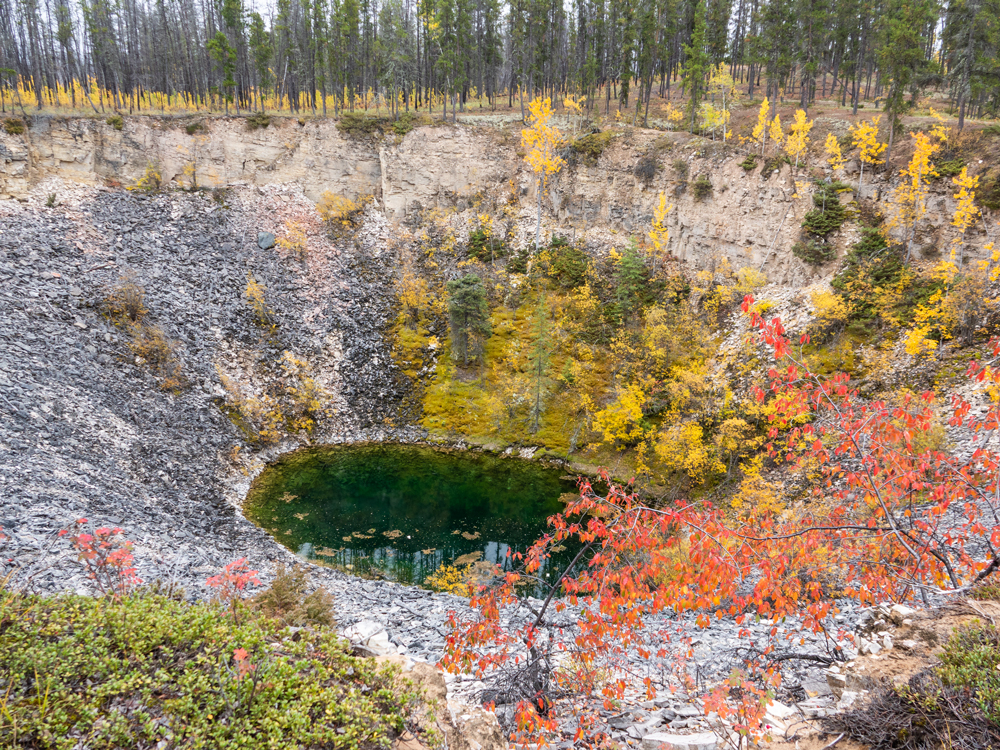 A circular water basin sits at the bottom of a deep funnel. The upper walls are tan with block lines running horizontally. Rocks and gravel cover the lower part, with some red, yellow, and green plants.